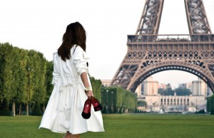 Woman barefoot in front of Eiffel Tower