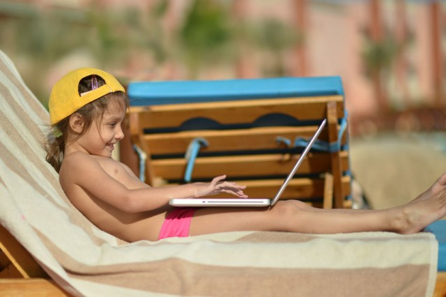 Digital parenting: Girl with laptop on beach