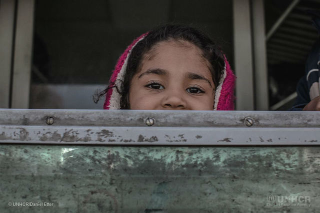 Iraqi child looks out of train crossing Balkans heading north to Europe.