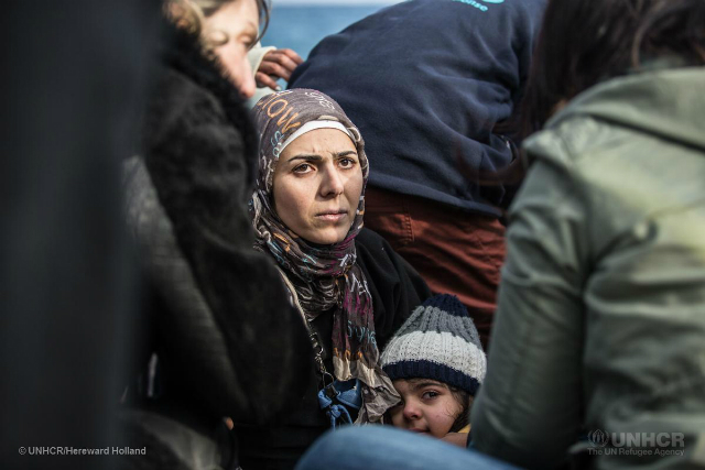 Refugee woman sits with child waiting for assistance ©UNHCR/ Hereward Holland