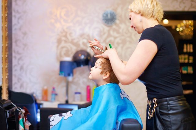 young boy getting haircut in salon